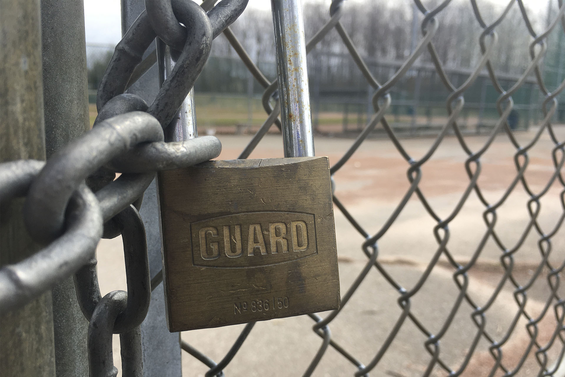 A lock on the gate to a baseball field.