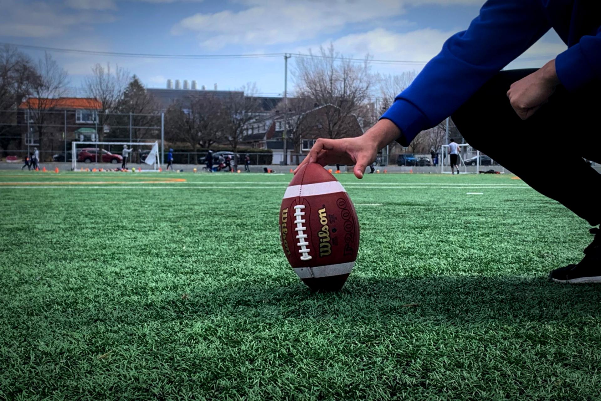 Tysen Otis-Copeland holds a football.