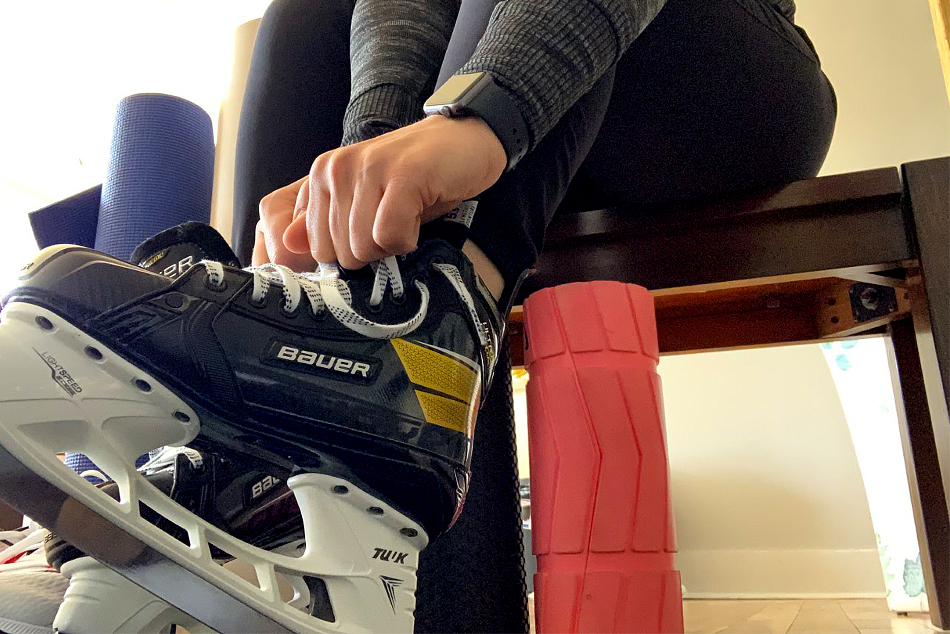 A woman tying her skates.